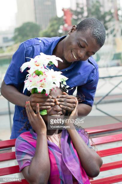 the young man made a surprise to his girlfriend, closing her eyes from behind her and with a flower - femme ivoirienne photos et images de collection