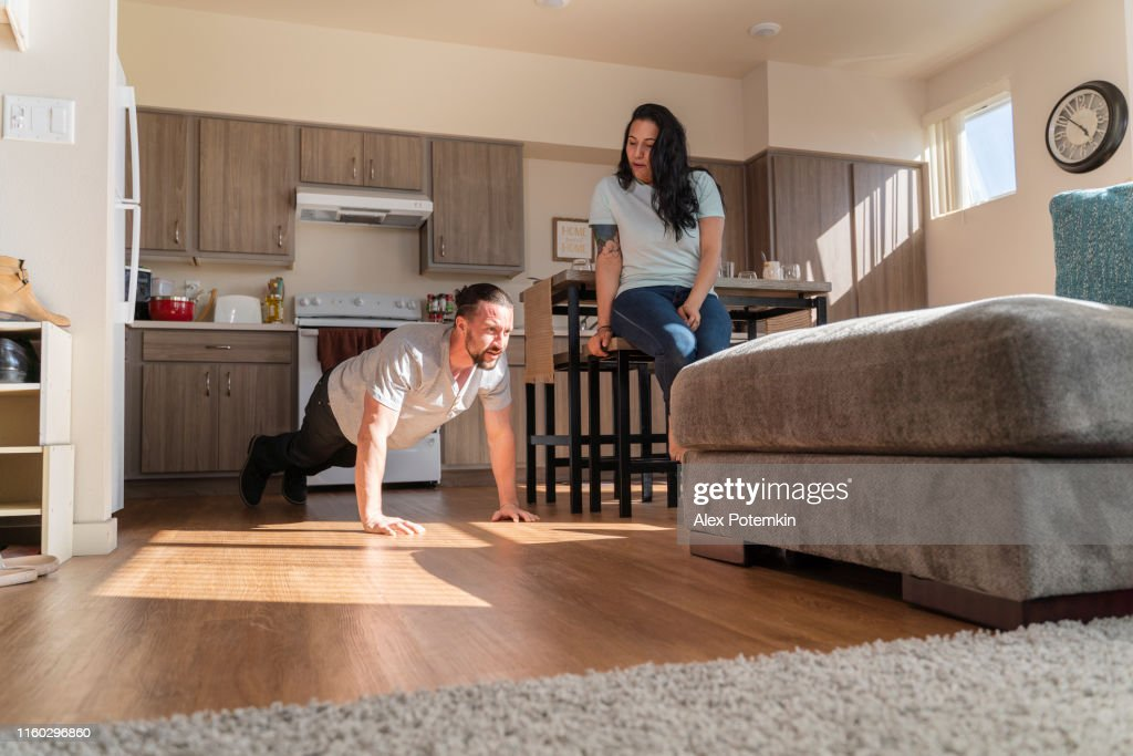 The young man pushing-up on the floor in the kitchen, with his roommates around. : Stock Photo