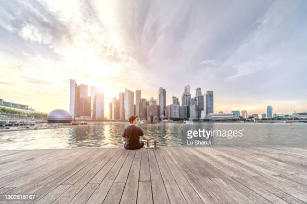 the young man sat on the dock with urban skyline and skyscrapers in marina bay singapore. - singapore stock pictures, royalty-free photos & images