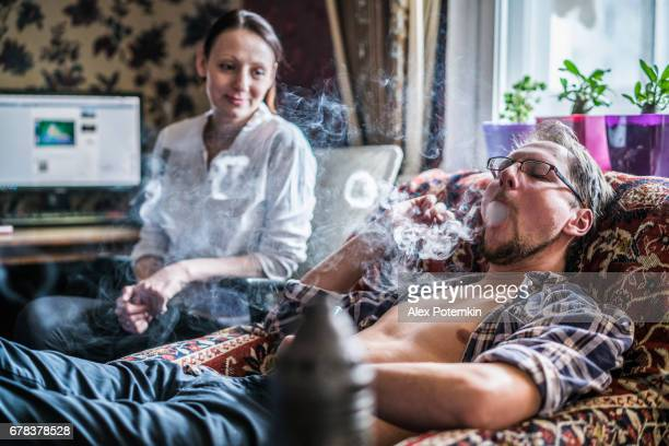 the young man smoking hookah, with his girlfriend in backdrop - hookah stock photos and pictures