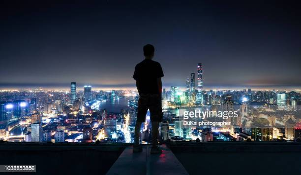 the young man stood on the roof and looked at the shanghai cbd - night stockfoto's en -beelden