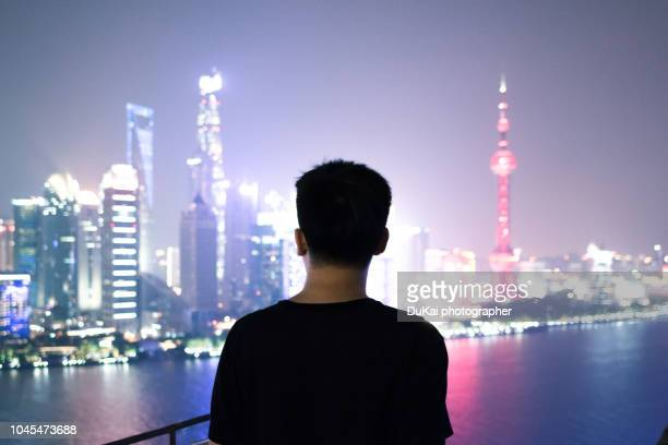 The young man stood on the roof and looked at the shanghai pudong CBD