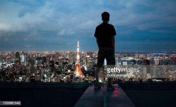 the young man stood on the roof and looked at the tokyo - tokyo japan stock pictures, royalty-free photos & images