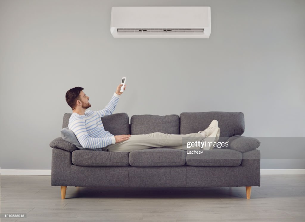 The young man turns on the air conditioner cools the air while sitting on the sofa in the room : Stock Photo