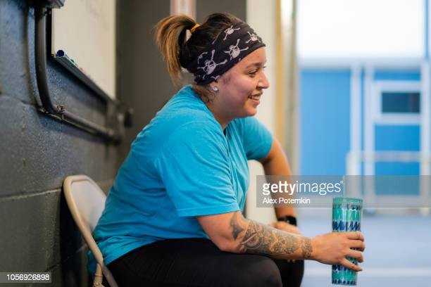 the young, pretty, body-positive latino woman wearing a tattoo, drinking the water and resting after the workout, tired and exhausted. - alex potemkin or krakozawr latino fitness stock photos and pictures