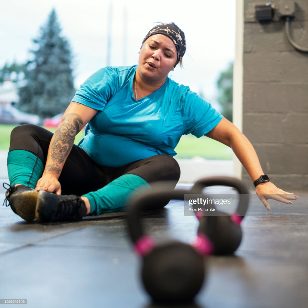 The young, pretty, body-positive Latino woman wearing tattoo finishing the workout, tired and exhausted. : Stock Photo