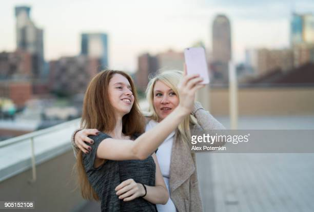 The young pretty pregnant woman with her little sister, the 16 years old teenager girl, hanging out together, taking selfies pictures with the smartphone and having fun at the rooftop