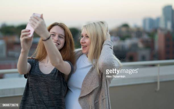the young pretty pregnant woman with her little sister, the 16 years old teenager girl, hanging out together, taking selfies pictures with the smartphone and having fun at the rooftop - 25 29 years stock pictures, royalty-free photos & images