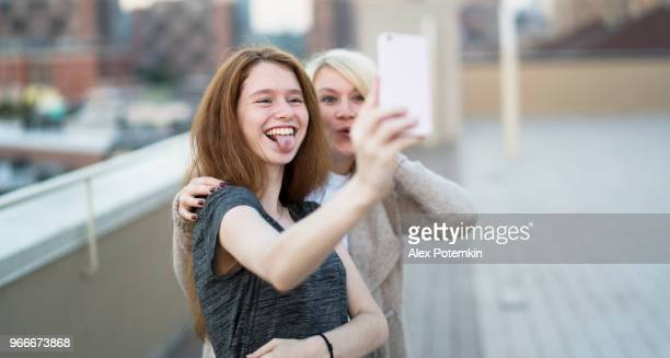 the young pretty pregnant woman with her little sister, the 16 years old teenager girl, hanging out together, taking selfies pictures with the smartphone and having fun at the rooftop - 16 17 years stock pictures, royalty-free photos & images