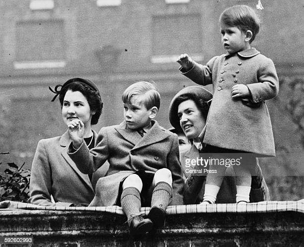 The young Prince Charles and Prince Richard of Gloucester playing on a wall with their nannies, at Clarence House in London, 1951.