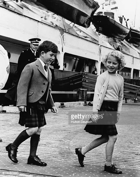 The young Prince Charles and Princess Anne of Great Britain leave the Royal Yacht Britannia on their way to visit the lighthouse on Stornoway during...