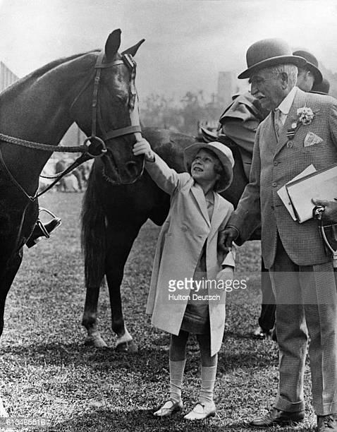 The young Princess Elizabeth, later Queen Elizabeth II strokes a horse.
