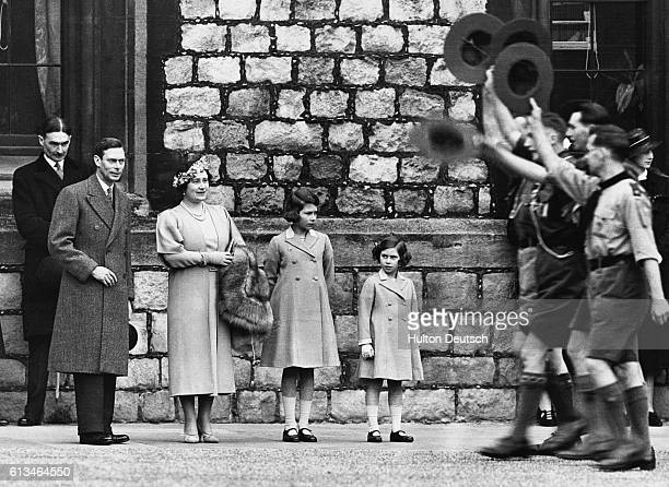 The young Princess Elizabeth watches a parade of Boy Scouts at Windsor Castle with her sister Margaret and her parents, the King and Queen.