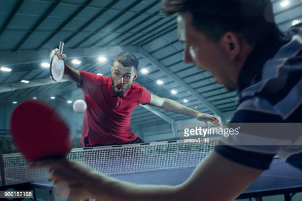 the young sports men tennis players in play on black arena background with lights - table tennis stock pictures, royalty-free photos & images