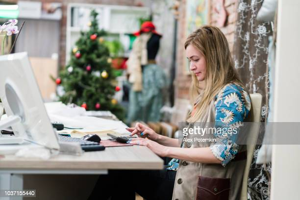 The young woman, designer, working in the modern small business office