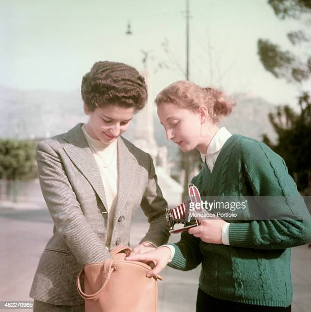 The young woman Giovanna Barbera searching her handbag while her friend Adriana Lanza is looking at her holding a bellows camera Palermo 1955