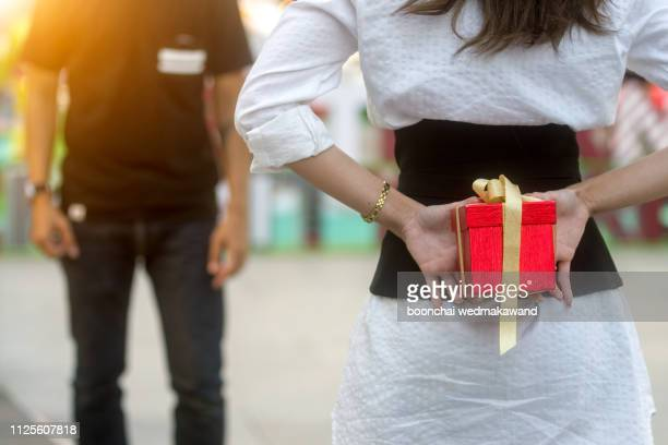 the young woman gives a gift to a young man in the cafe - boyfriend stock pictures, royalty-free photos & images