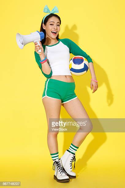 the young woman holding a megaphone and football - asian cheerleaders stock photos and pictures