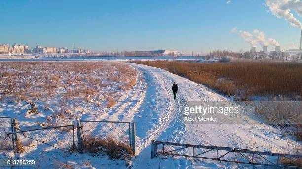 The young woman running and walking on the snowy country road. Aerial low-altitude drone photo.