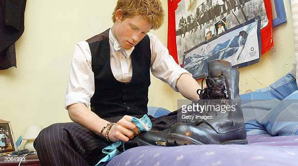 The youngest son of the Prince of Wales Prince Harry polishes his own Combined Cadet Force boots on May 12 2003 in his room at Eton College Eton in...