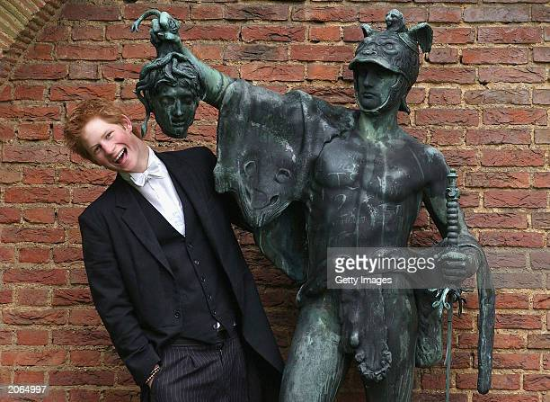 The youngest son of the Prince of Wales Prince Harry poses next to a bronze statue of Perseus holding the Gorgon's head on May 12 2003 in the King of...