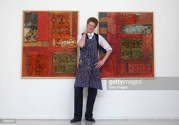 The youngest son of the Prince of Wales Prince Harry stands between two of his artworks on May 12 2003 in the Drawing School at Eton College Eton in...