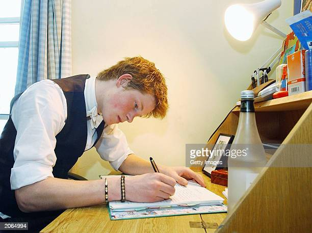 The youngest son of the Prince of Wales Prince Harry studies at his desk on May 12 2003 in his room at Eton College Eton in England Prince Harry will...