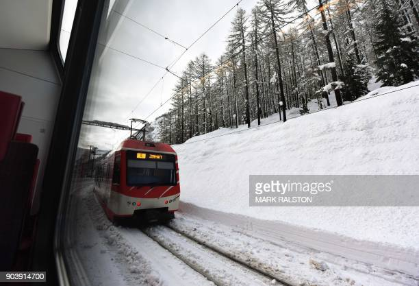 The Zermatt to Tasch train passes by large snow mounds, as train services resumed to evacuate tourists after heavy snowfall and avalanches had...