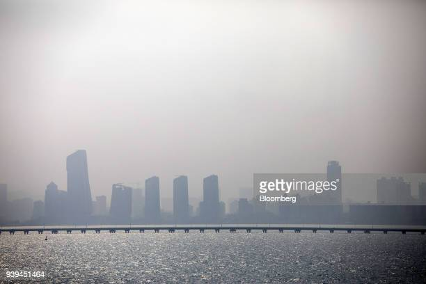 The Zhuhai skyline stands beyond a bridge seen from a section of the Hong KongZhuhaiMacau Bridge during a media tour offshore in Zhuhai China on...