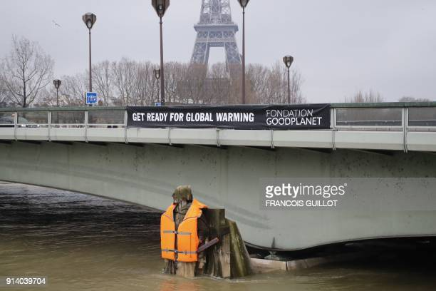 The Zouave statue of the Pont D'Alma bridge standing partially submerged after the River Seine burst its banks in Paris wears a life jacket put by...