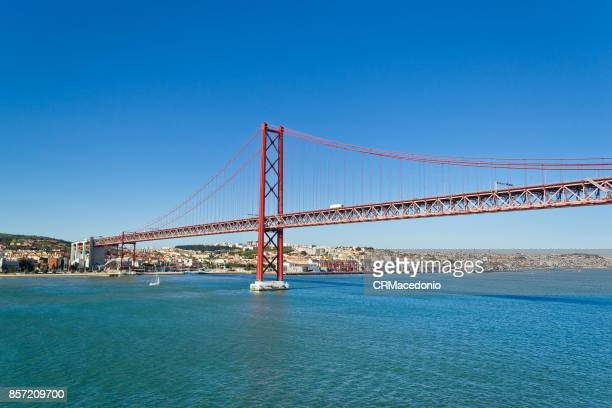 the 25 de abril bridge (ponte 25 de abril) under blue sky. - crmacedonio stock-fotos und bilder