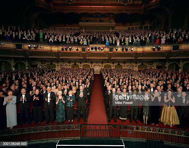 Theater audience standing in formal attire, applauding