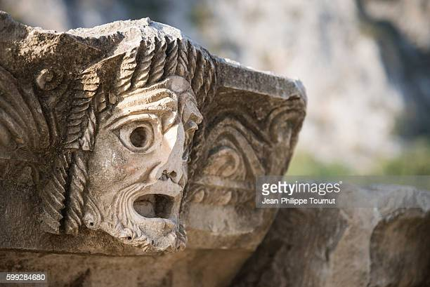 Theater mask, man face with broken nose carved on stone in the archaeological site of Myra, ancient Lycian civilisation, Southern Turkey