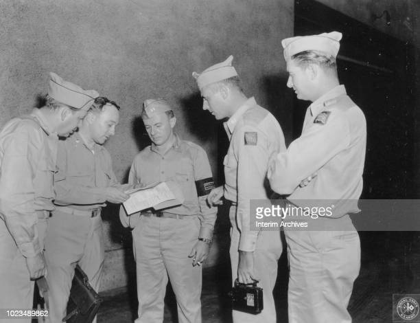 Theater Photographic Officer Far East Command Major Marshall Berard shows his orders to unidentified friends who came to see him off aboard the USAT...