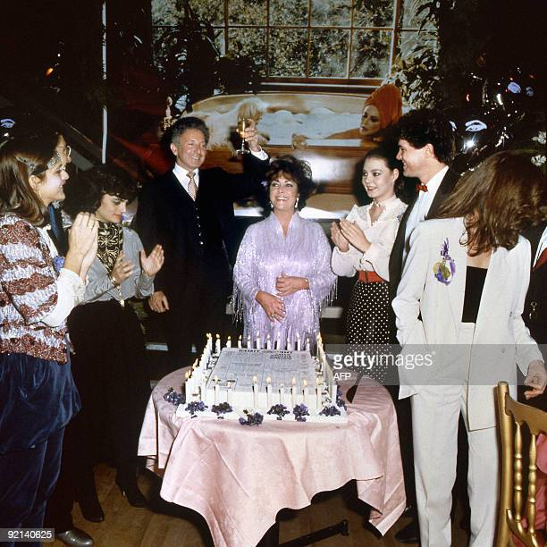 Theater producer Zev Bufman raises his glass to toast actress Elizabeth Taylor during her 50th birthday party at Legends, the London nightclub....