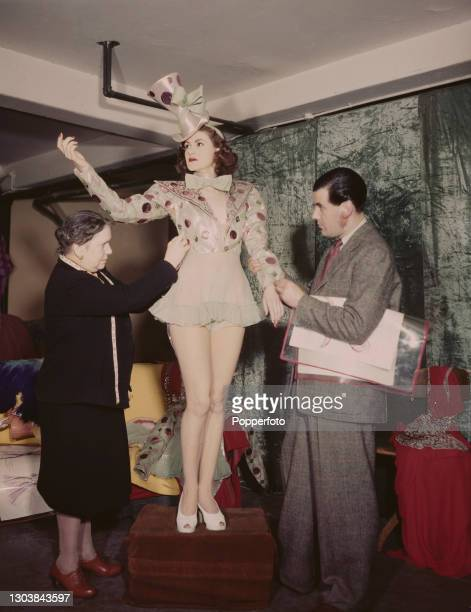 Theatre costume designer Robert St John Roper , with help from a dresser, makes final adjustments to a stage costume worn by Margot Harris at the...