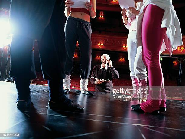 Theatre Director Looking Up at Dancers Rehearsing on Stage