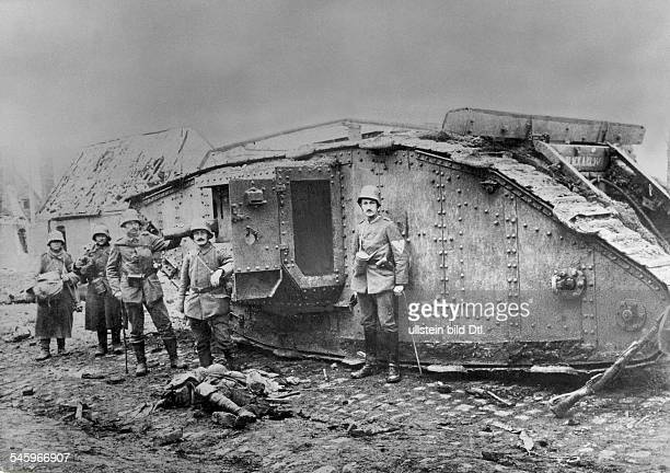1WW Theatre of war western front 1917 Battle of Cambrai 2011 German soldiers in front of a broken down British tank 'Mark IV' at the outskirts of...