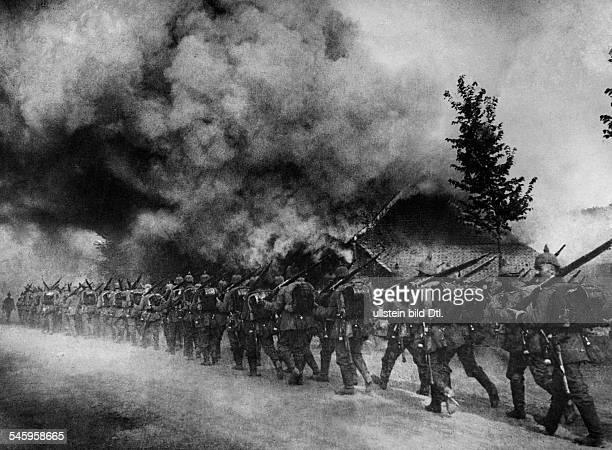 1WW Theatre of war western front BelgiumFrance augustseptember1914 German infantry column marching through a burning village in belgium August 1914