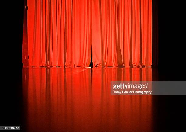 Theatrical red curtains on black background.