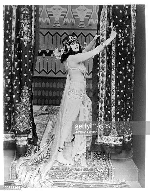 Theda Bara holds onto a curtain in a scene from the film 'Cleopatra' 1917