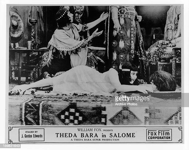 Theda Bara laughs at a severed head in a scene from the film 'Salome' 1918