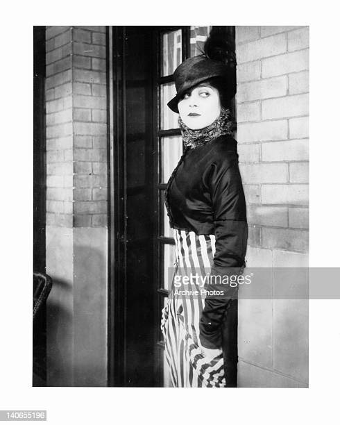 Theda Bara leaning against brick wall in a scene from the film 'A Fool There Was' 1915