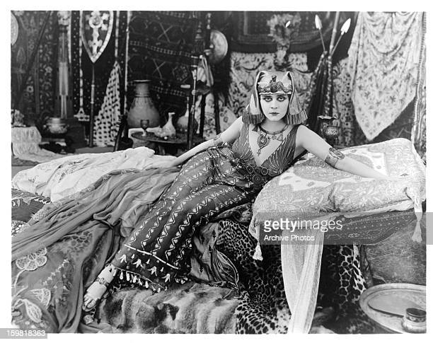 Theda Bara sits on a bed of cushions in a scene from the film 'Cleopatra' 1917