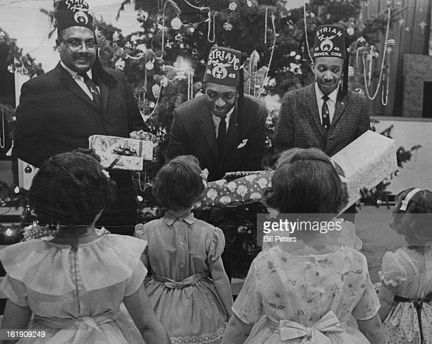 DEC 18 1964 DEC 20 1964 Their Christmas is a Little Brighter Members of Syrian Temple No 49 of Prince Hall Masons hand out presents Friday to little...