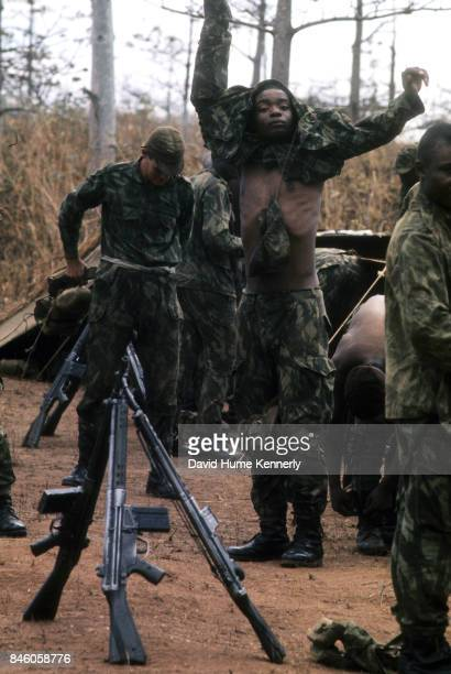 Their rifles arranged in stacks Colonial Portuguese soldiers dress outside camp tents during training Ancuabe Cabo Delgado Province Mozambique July...
