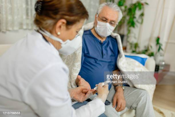 theme diabetes.the man whose glucose was measured by going to the home of healthcare professionals. it uses the technology of an instrument for measuring the level of glucose in the blood - diabetes stock pictures, royalty-free photos & images