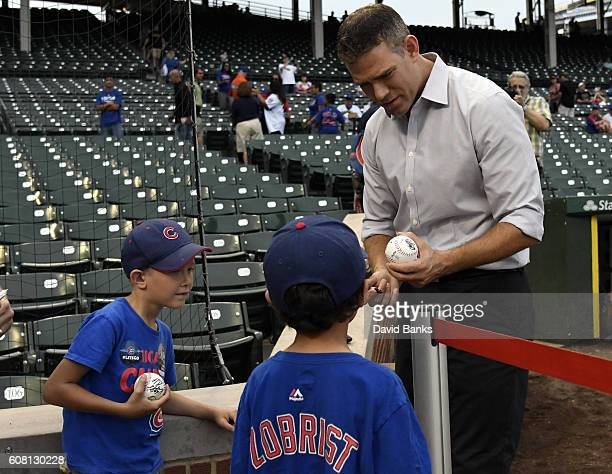Theo Epstein President of Baseball Operations for the Chicago Cubs signs autographs before the game between the Chicago Cubs and the Cincinnati Reds...