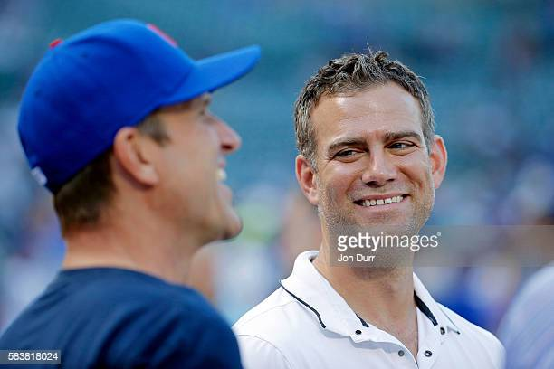 Theo Epstein President of Operations for the Chicago Cubs talks with head football coach Jim Harbaugh of the University of Michigan before the game...
