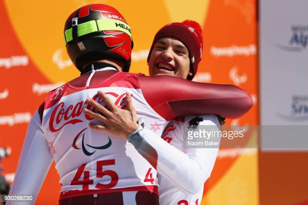 Theo Gmur of Switzerland celebrates with fellow team mate Michael Bruegger following his race during the Men's Standing Super G Alpine Skiing during...